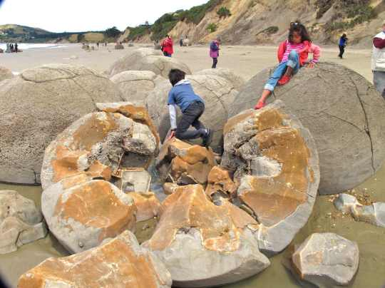 Niños jugando entre las piedras Moeraki