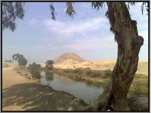 C.  Vista hacia la pirámide de bloques de barro desde el canal en Hawara