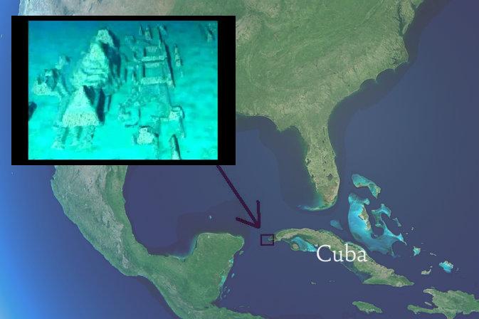 Cuba visto desde el espacio en el mapa de América del Norte. (Shutterstock*). La flecha apunta a la costa oeste de Cuba, donde en 2001 descubrieron estructuras de piedra bajo el agua, por Pauline Zalitzki y Paul Weinzweig. (Captura de pantalla/The Cosmos News/Youtube)
